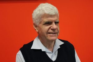 Radio Reading Champion Stephen Jolley: Smiling man with white hair, shirt and vest in front of a bright red background.