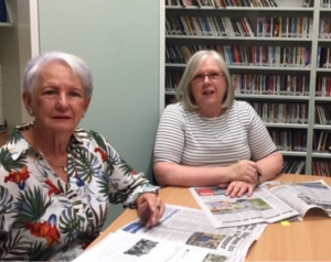 Cathy and Sharon sit at a table with open newspapers in 2MCE's resource room.